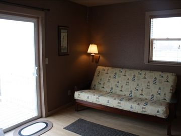 Family room with 2 person fouton. Sliding door opens to deck & Betsie Lake Bay