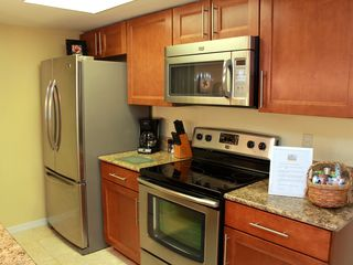 Kitchen with new triple door stainless steel refrigerator, stove and microwave - Royal Palm Bay villa vacation rental photo