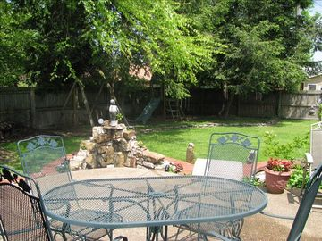 Large backyard, fenced in, fountain, swingset for kids, swing for adults.
