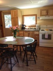 Newport cottage photo - Kitchen with stove, refrigerator, microwave, coffee maker and cooking utensils.