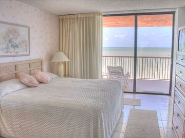 Master bedroom with king size bed with beach views and sliders to the balcony.