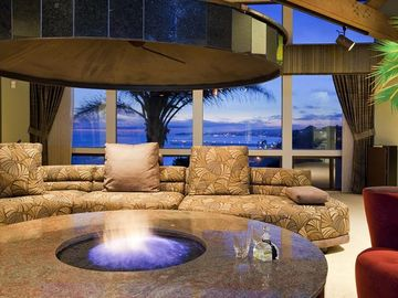 Living room with ocean and coastal lights view
