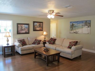 This spacious open living room is open to the kitchen, and dining area