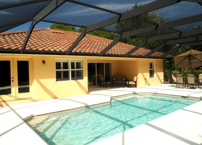 Heated pool with patio and sitting area under screened lanai.