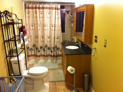 Comfy Bathroom with Massage Showerhead, stocked towel/linen cabinet and granite
