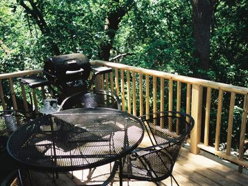 Deck with grill overlooking wooded hillside