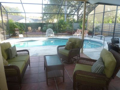 Large Lanai with screened in pool. Patio with fire pit in background.