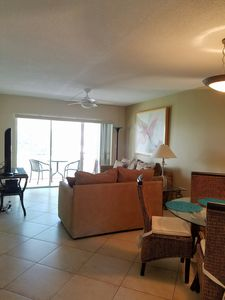 Living room and dinning area with ceiling fan, and a 55 inch flat screen tv.