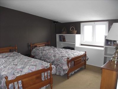 This bedroom in spacious with two beds, closet space, drawers & flat screen TV.