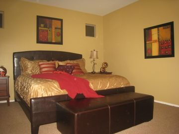 large master bedroom with king bed, seating area, flatscreen tv & adjoining bath
