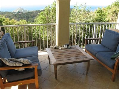 Veranda has dining table as well as two couches and spectacular view.