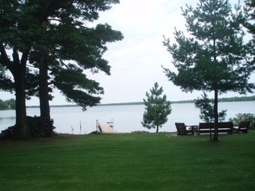 View of lake, dock, boat lift, and fire pit