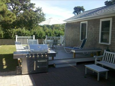 Outdoor hard piped gas grill and plenty of seating with movable fire pit