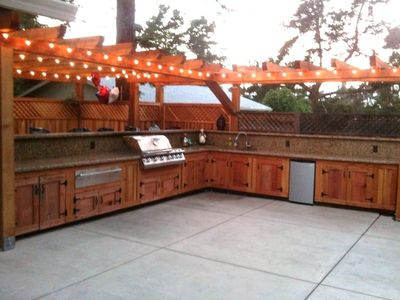 Big outdoor kitchen with seating on the back side of the grill.