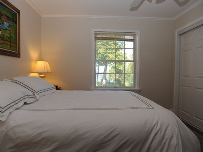 Bedroom with queen bed and view of the St. Lawrence River and gardens