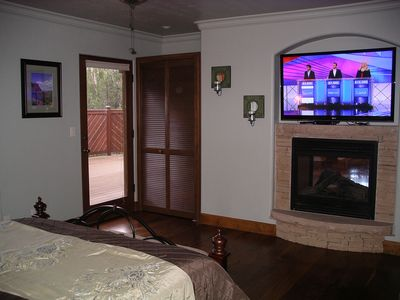master bedroom fireplace, bigscreen and door to deck