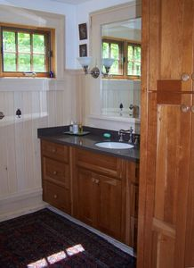 Bath sink, mirror, and cherry wood cabinets.