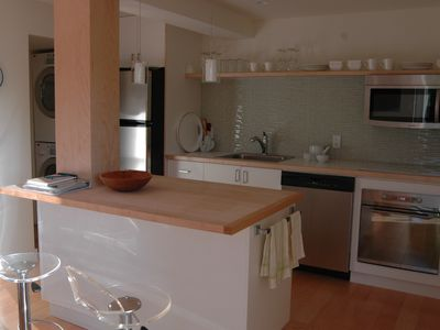 Garden suite's kitchen with stainless steel appliances and washer and dryer