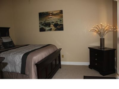 Queen size bed in contemporary furnished bedroom