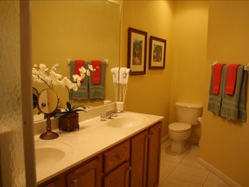 Master Bathroom with double sinks and large tiled walk in shower with bench.