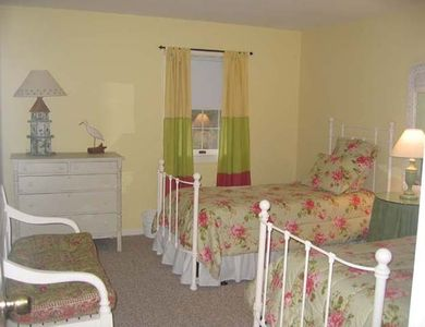 The twin bedroom is charming and features two twin beds and two windows.