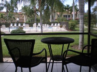Court of Palms condo photo - Screened in patio with view of the pool
