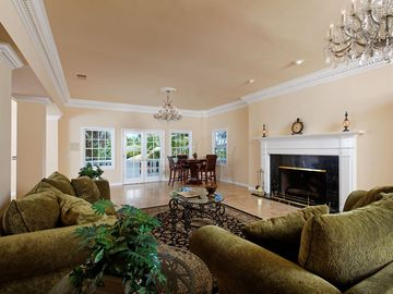 Elegant formal living room, fireplace, with access to pool and outdoor dinning.