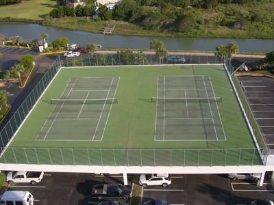 Tennis courts over parking area, may need racket and balls.