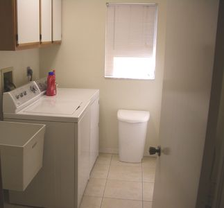 Laundry room with utility sink, washer & dryer and storage cabinets.