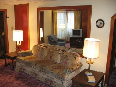 Lake Placid house rental - Living Room sofa across from fireplace. In left of picture: doorway to kitchen.