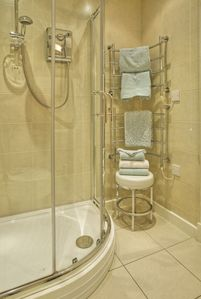 Spacious curved walk-in shower cabinet and full-length heated towel-rail