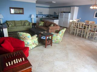 Ocean Drive Beach condo photo - Open living room with attached kitchen, dining room and oceanfront balcony.