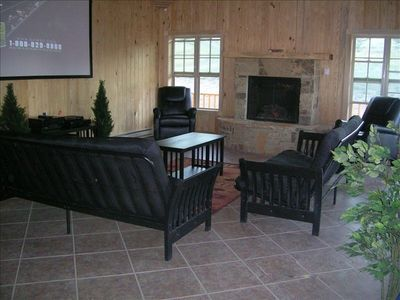 Large living room with stone fireplace, 100 inch tv, 1000 watt surround sound