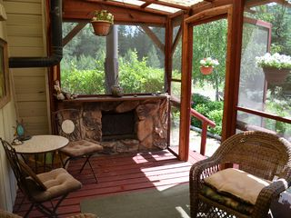 Lake Roosevelt house photo - Fireplace on screened in sleeping porch. View of pond area and herb garden