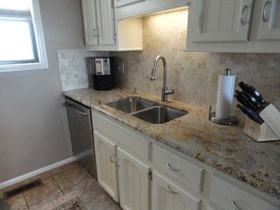 Our new kitchen with granite counter and custom tile backsplash