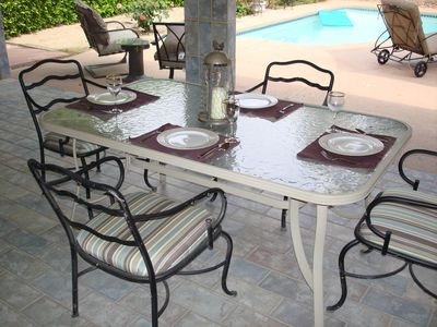 Covered patio table set for four overlooking the pool