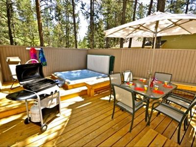 Private enclosed patio deck with hot tub, dining table for 6 and gas grill.
