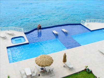 65 ft. pool with Jacuzzi on the waters edge. Dark blue is shallow water lounge
