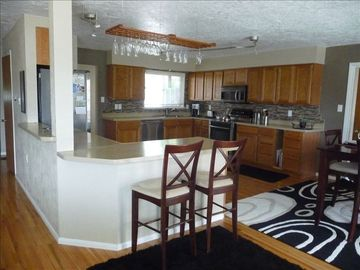 Large spacious kitchen, featuring stainless appliances, wine bar, track lights