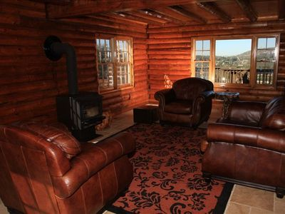 Downstairs living room with wood-burning stove and leather sofa and chairs.