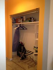 South Beach studio photo - closet with ironing board & beach chairs.