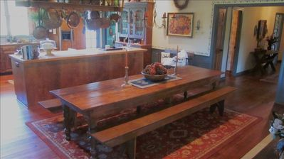 Dining table which seats 12 with large island and kitchen beyond.