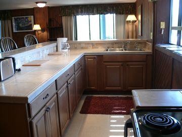 Newly remodeled kitchen with bar and four stools for enjoying meals together.