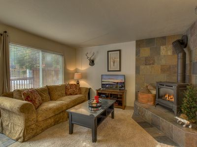 The living room opens to the front deck and has a gas fireplace and flatscreen TV.