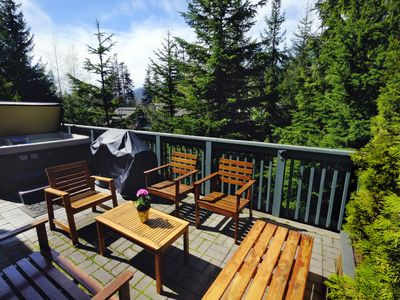 Large sunny deck with private hot tub and 2 seating areas.