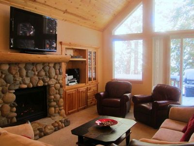 Family room with stone fireplace, large flat screen TV , and comfortable seating