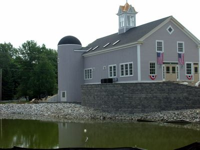 Side of the barn with the pond