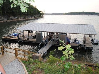 Private boat dock with just a few stairs at the end of a gently sloping path.