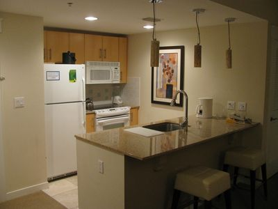 well equipped kithen with bar stools at granite counter, opens to living room