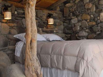 cozy queen bed with down comforter and down pillows in the River Bed